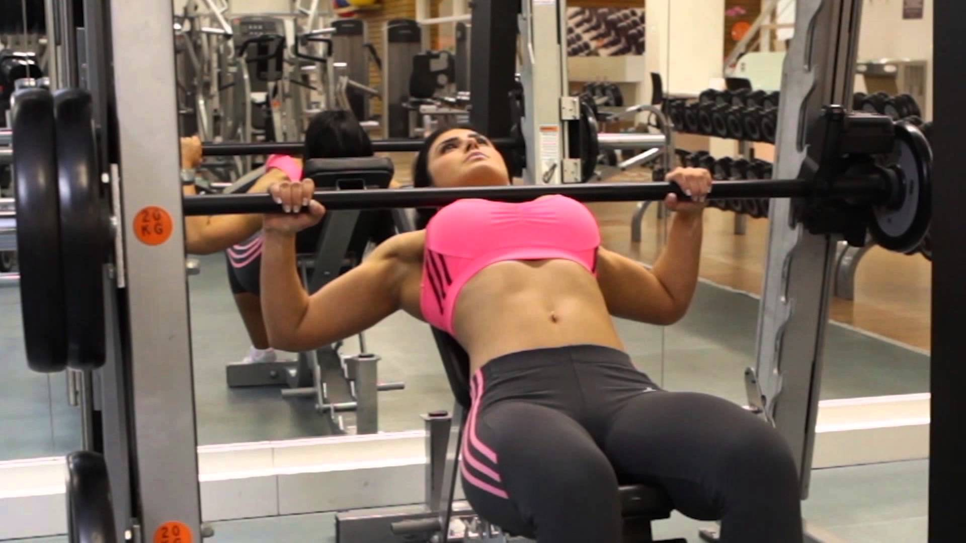 smith machine bench press by woman in gym